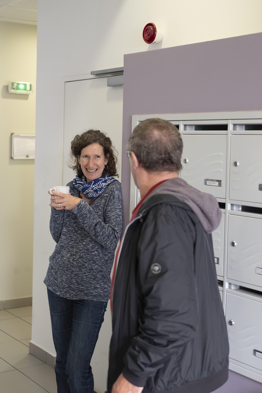 Des résidents de logements sociaux discutent devant des boîtes aux lettres